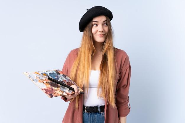 Młoda artysta kobieta trzyma paletę odizolowywającą na błękit ściany pozyci i patrzeje strona