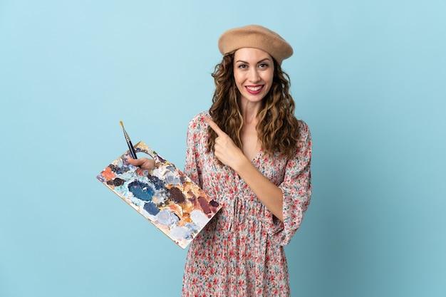 Młoda artystka dziewczyna trzyma paletę na białym tle na niebieskim tle, wskazując na bok do przedstawienia produktu
