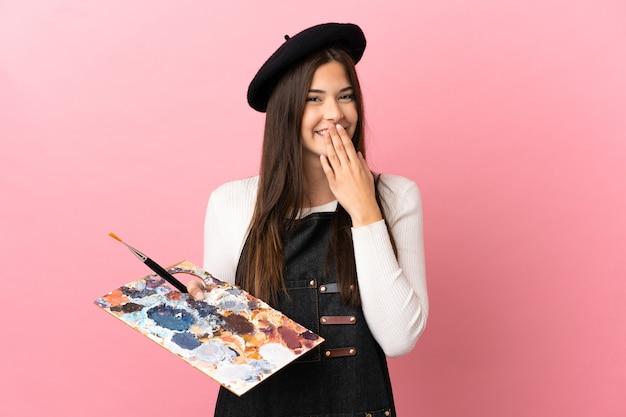 Młoda artystka dziewczyna trzyma paletę na białym tle różowym tle szczęśliwa i uśmiechnięta obejmująca usta ręką