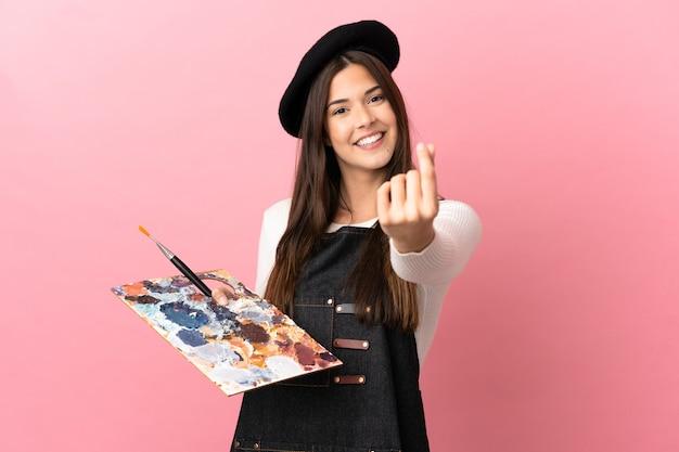 Młoda artystka dziewczyna trzyma paletę na na białym tle różowym tle robi pieniądze gest