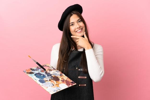 Młoda artystka dziewczyna trzyma paletę na różowym tle szczęśliwa i uśmiechnięta