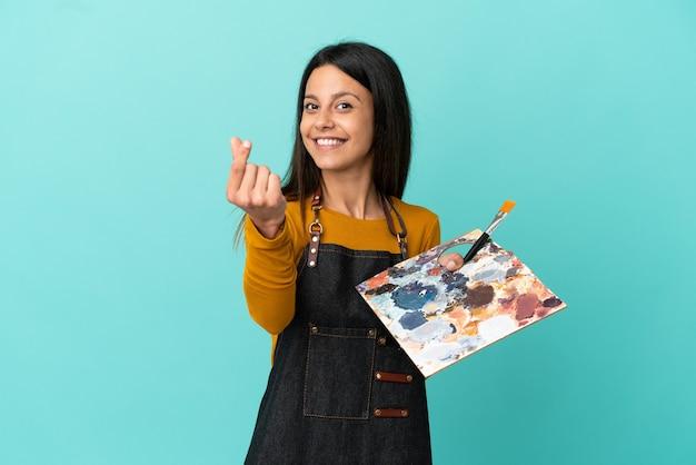 Młoda artystka kaukaska kobieta trzyma paletę na białym tle na niebieskim tle robi gest pieniędzy