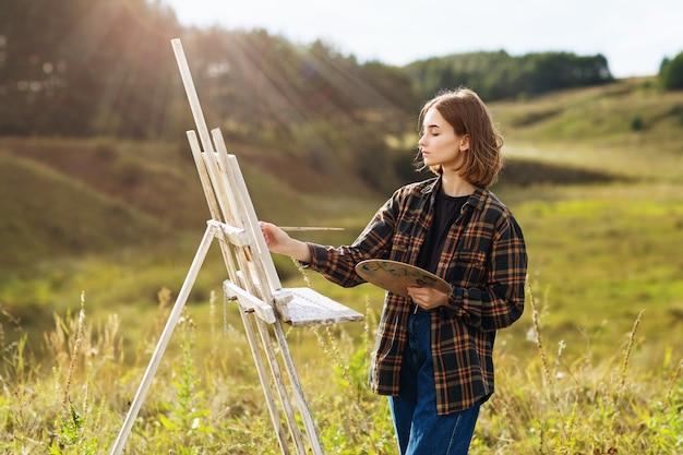 Młoda artystka maluje obraz w naturze w słoneczny letni wieczór