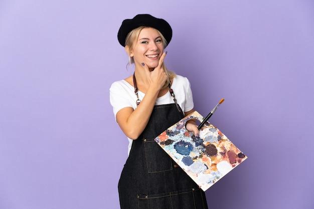 Młoda artystka rosjanka trzymająca paletę na fioletowym tle szczęśliwa i uśmiechnięta