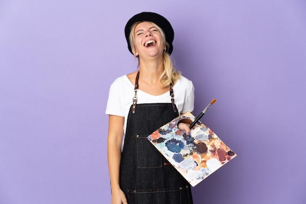 Młoda artystka rosjanka trzymająca paletę odizolowaną na fioletowym tle śmiejąc się