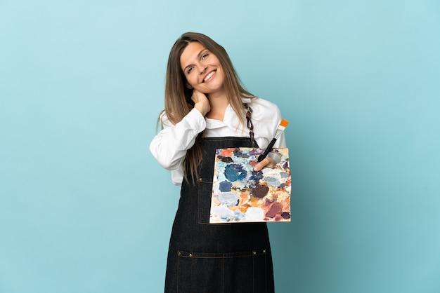 Młoda artystka słowacka kobieta odizolowana na niebieskim tle śmiejąc się