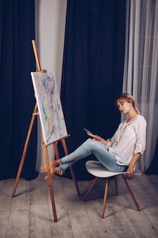 Młoda artystka w białej koszuli i niebieskich dżinsach, maluje obraz na płótnie w warsztacie. młody student używa pędzli, płócien i sztalug. kreatywna praca dla dzieci i dorosłych.