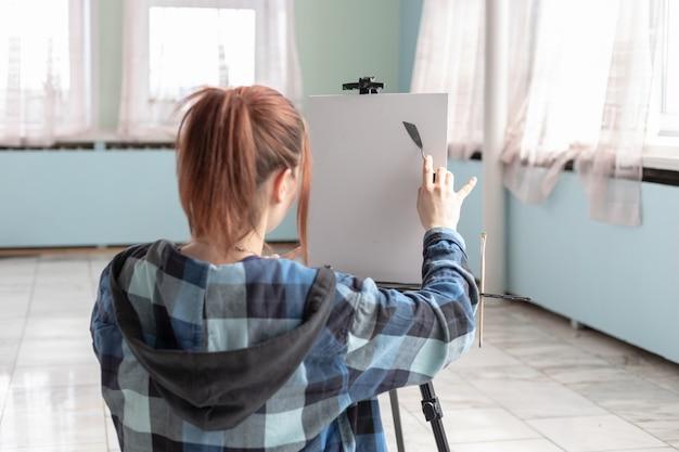 Młoda artystka z nożem w ręku przygotowuje się do malowania obrazu olejnego. białe płótno z miejscem do kopiowania znajduje się na czarnej sztaludze.