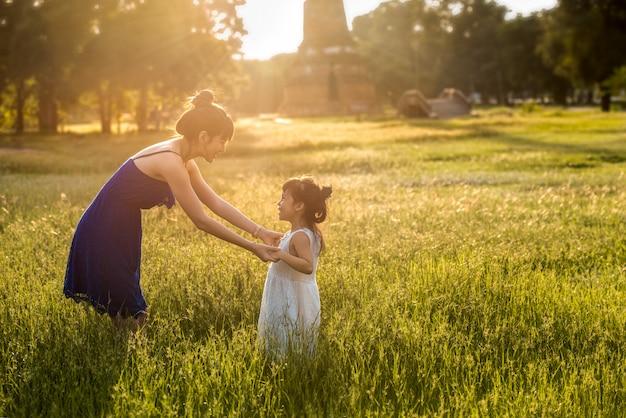Młoda asia matka ma zabawę z córką w polu z światłem słonecznym na trawie