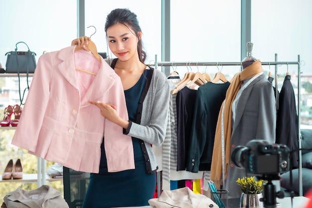 Młoda asia szczęśliwa blog wideo na żywo (vlogger) i sprzedaż ubrań podczas zakupów w sklepie internetowym.