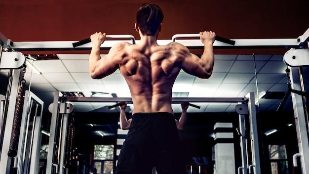 Młoda atleta ćwiczy na barach w gym