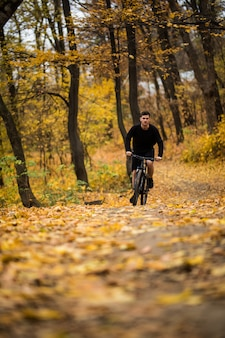 Młoda atleta jedzie z bicyklem na jesień parku. przygotowanie do treningu