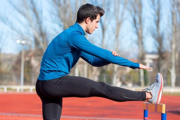 Młoda atleta rozciąga się na bieżni.