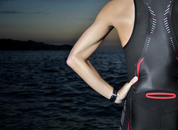 Młoda atleta triathlon przed wschodem słońca nad morzem