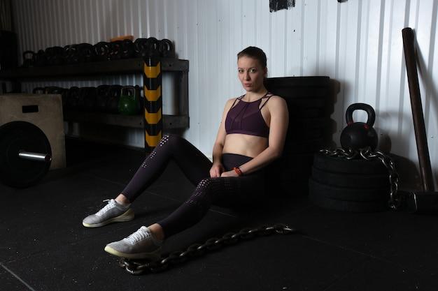 Młoda atletka w fioletowym sportowym topie i szarych leginsach siedzi na podłodze w hali sportowej w pobliżu sprzętu sportowego