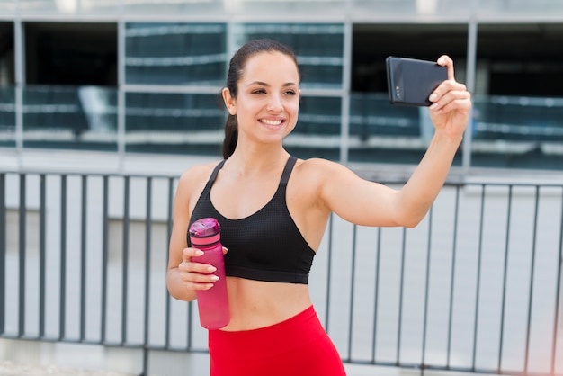Młoda atlety kobieta z smartphone
