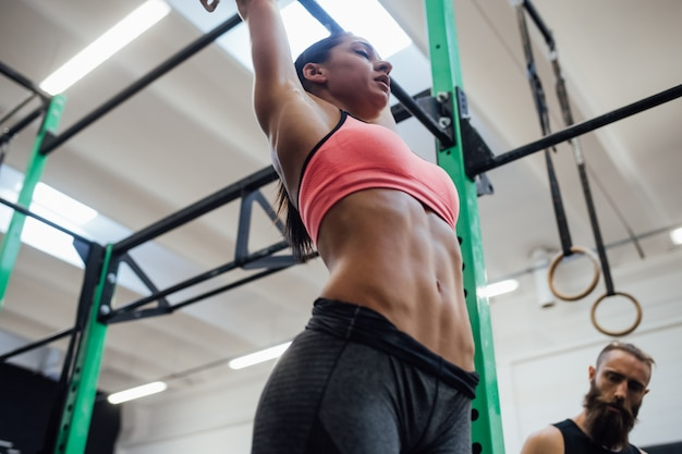 Młoda atletyczna kobieta robi pull up w gimnastycznym barze wspomagany przez osobistego trenera