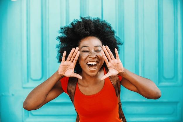 Młoda atrakcyjna afrykańska kobieta krzyczy na zewnątrz.
