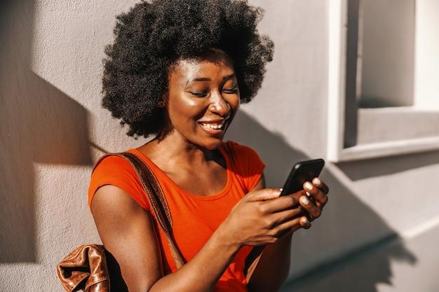 Młoda atrakcyjna afrykańska kobieta stojąca na zewnątrz i za pomocą inteligentnego telefonu.
