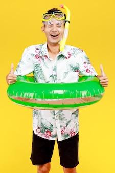 Młoda atrakcyjna azjatka ma na sobie kapelusz i białą hawajską koszulę na sobie żółtą maskę do nurkowania i zielony pierścień pływacki wokół talii na żółtym tle. koncepcja na wakacje na plaży.