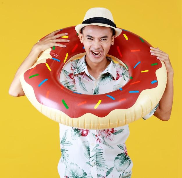 Młoda atrakcyjna azjatka nosi kapelusz i białą hawajską koszulę z czerwonymi i zielonymi wzorami kwiatowymi i pierścieniem pływackim wokół szyi, wybierając się na wakacje na plaży na żółtym tle.