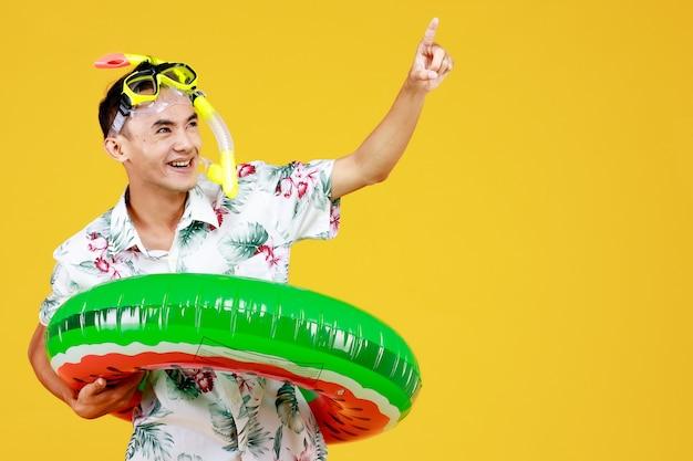 Młoda atrakcyjna azjatka w białej koszuli hawajskiej na sobie żółtą maskę do nurkowania i zielony pierścień pływacki w talii, wskazując palcem w powietrze na żółtym tle. koncepcja na wakacje na plaży.