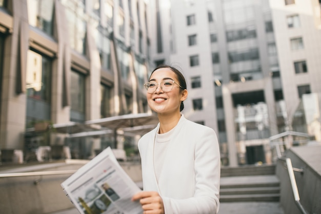 Młoda atrakcyjna azjatycka bankierka lub księgowa w okularach czyta gazetę poza nowoczesnym centrum biurowym