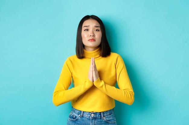 Młoda atrakcyjna azjatycka dziewczyna błagająca o przysługę, potrzebująca czegoś i prosząca, trzymająca się za ręce w modlitwie, stojąca na niebieskim tle.