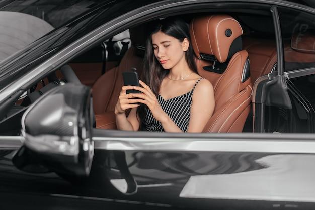 Młoda atrakcyjna azjatycka kobieta korzystająca z telefonu siedząc w luksusowym samochodzie przed morzem
