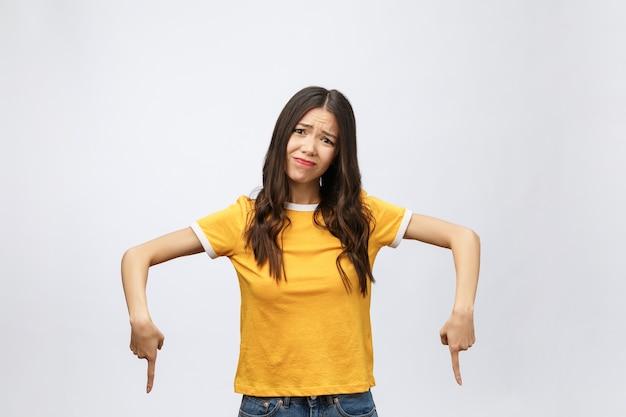 Młoda atrakcyjna azjatycka kobieta, która wskazuje na palec z nieszczęśliwą emocją