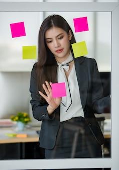 Młoda atrakcyjna azjatycka kobieta w czarnym biznesie, czytanie i pisanie na zaksięgowaniu go na szklanym panelu w nowocześnie wyglądającym biurze z rozmytym tłem okien. koncepcja nowoczesnego stylu życia w biurze.