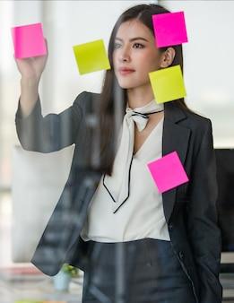 Młoda atrakcyjna azjatycka kobieta w czarnym biznesie, czytanie i pisanie na zaksięgowaniu go na szklanym panelu w nowocześnie wyglądającym biurze z rozmytym tłem windows. koncepcja nowoczesnego stylu życia w biurze.