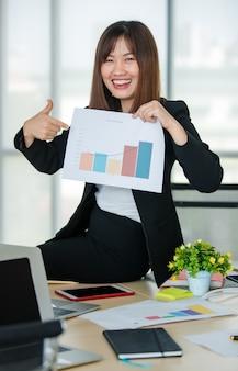 Młoda atrakcyjna azjatycka kobieta w czarnym garniturze siedzi na stole pokazując wykresy na papierze w nowocześnie wyglądającym biurze z rozmytym tłem windows. koncepcja nowoczesnego stylu życia w biurze.