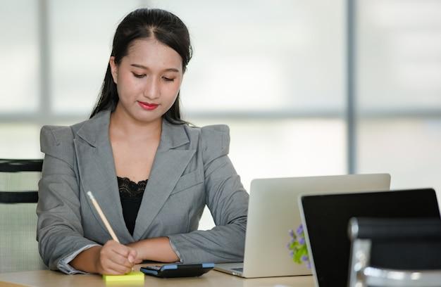 Młoda atrakcyjna azjatycka kobieta w szarym garniturze siadając pisania z filiżanką kawy i laptopem na stole w nowocześnie wyglądającym biurze. koncepcja nowoczesnego stylu życia w biurze.