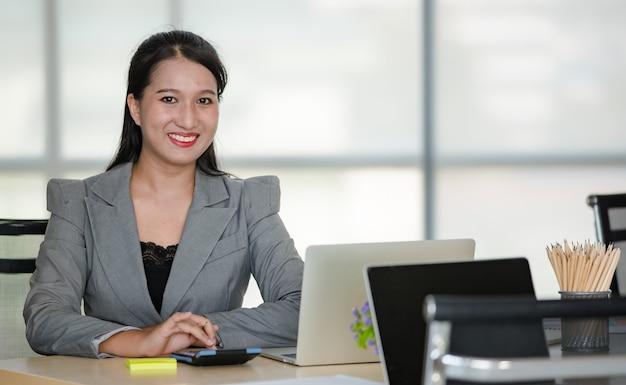 Młoda atrakcyjna azjatycka kobieta w szarym garniturze siedzi uśmiechając się z filiżanką kawy i laptopem na stole w nowocześnie wyglądającym biurze. koncepcja nowoczesnego stylu życia w biurze.