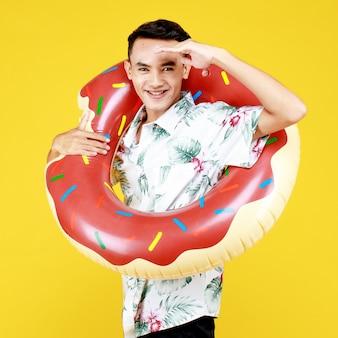 Młoda atrakcyjna azjatycka mężczyzna ubrany w kapelusz i białą koszulę hawajski i pierścień pływać pączek wokół jego ciała na żółtym tle. koncepcja na wakacje na plaży.