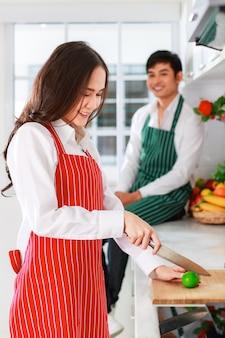 Młoda atrakcyjna azjatycka para w kuchni. kobieta ubrana w czerwony fartuch krojenie cytryny przygotowuje się do gotowania i mężczyzna siedzi w tle ubrany w zielony fartuch. koncepcja zdrowej i szczęśliwej miłości i gotowania.