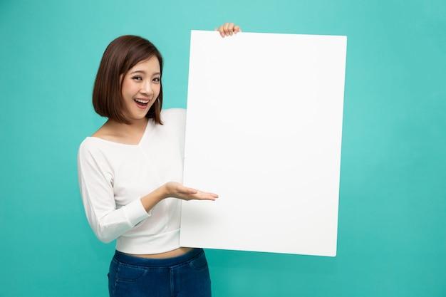 Młoda atrakcyjna azjatykcia kobieta pokazuje pustą białą deskę i trzyma