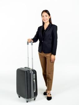 Młoda atrakcyjna bizneswoman azjatyckich w garniturze niosąc swoją czarną walizkę w podróż służbową i patrząc na kamery