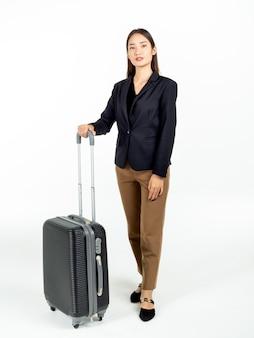 Młoda atrakcyjna bizneswoman azji w garniturze niosąc jej czarną walizkę w podróż służbową na białym tle