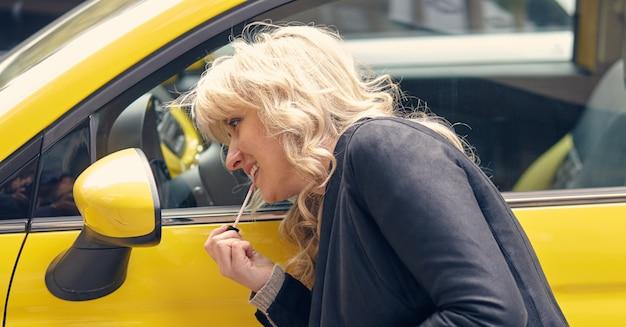 Młoda atrakcyjna blond kobieta maluje usta, patrząc w lusterko boczne żółtego samochodu