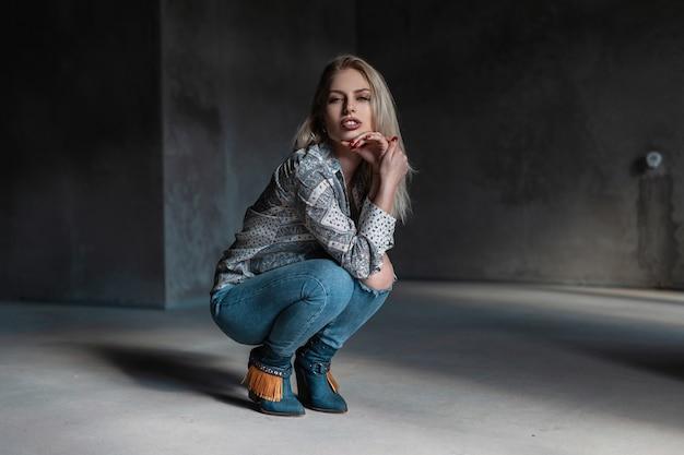 Młoda atrakcyjna blond kobieta w modnych zielonych butach kowbojskich w koszuli vintage w stylowych dżinsach zgrywanie siedzi w ciemnoszarym pokoju