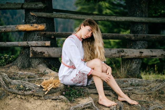 Młoda atrakcyjna blondynka boso w białej sukni z ornamentem, siedząc w pobliżu drewnianego płotu na zewnątrz