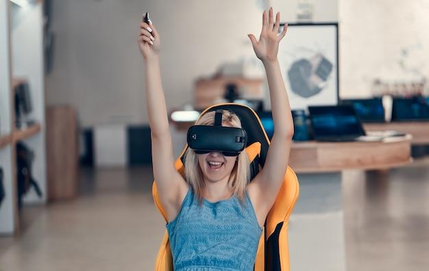 Młoda atrakcyjna blondynka rasy kaukaskiej wypróbowuje technologię wirtualnej rzeczywistości i siedzi na krześle. wnętrze sklepu technicznego.