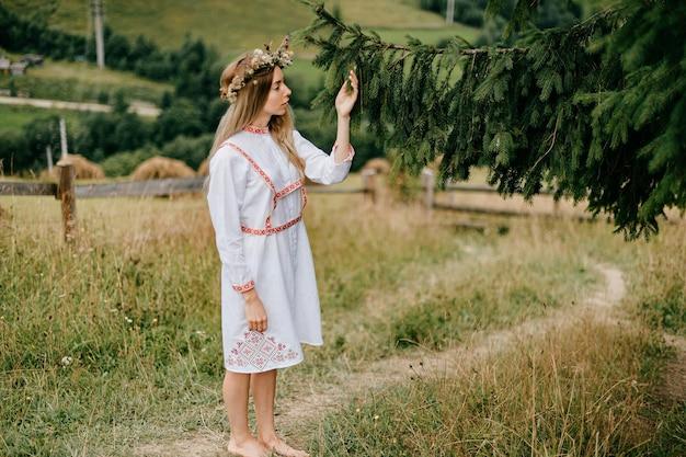 Młoda atrakcyjna blondynka w białej sukni z haftem i wieńcem kwiatów na głowie pozowanie z gałęzi jodły na krajobraz wsi
