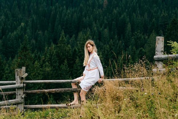 Młoda atrakcyjna blondynka w białej sukni z haftem siedzi na drewnianym płocie nad malowniczym lasem