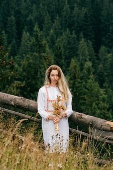 Młoda atrakcyjna blondynka w białej sukni z haftem z bukietem kłosków na łące nad malowniczym krajobrazem