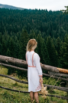 Młoda atrakcyjna blondynka w białej sukni z haftem z bukietem kłosków w pobliżu drewnianego ogrodzenia nad malowniczym krajobrazem