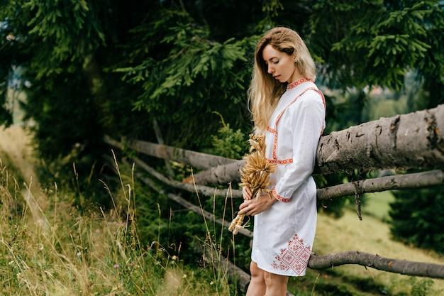 Młoda atrakcyjna blondynka w białej sukni z haftem z bukietem kłosków w pobliżu drewnianego ogrodzenia