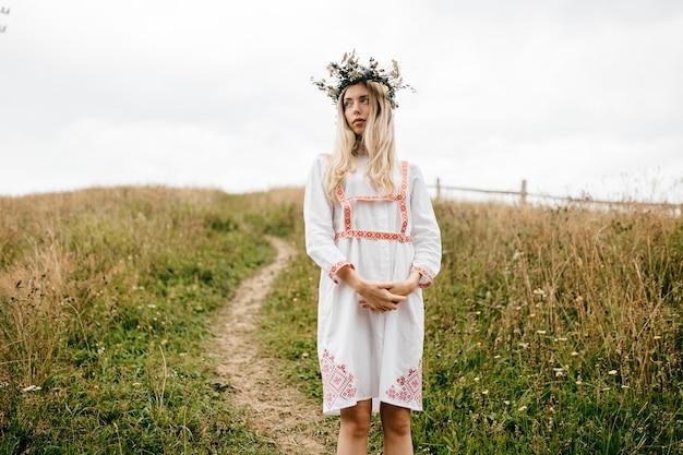 Młoda atrakcyjna blondynka w białej sukni z ornamentem i wieńcem kwiatów na głowie pozowanie w polu